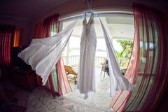 婚礼礼服在水池、海洋和山的背景的旅馆 免版税库存图片