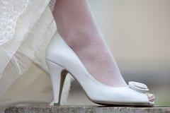 婚礼礼服妇女的鞋子和吊边  新娘的腿一双白色鞋子的 库存图片