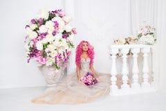 婚礼礼服摆在的妇女 塑造象一个玩偶,在内部演播室射击, 免版税库存图片