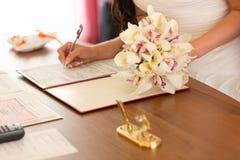 婚礼礼服的一个女孩签署了一个重要文件 库存图片