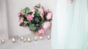 婚礼礼服的一个性感的新娘坐椅子 女孩为她的婚礼做准备 影视素材