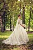 婚礼礼服的典雅的新娘与在全长的被浸洗的吊边在森林或公园的背景 库存照片