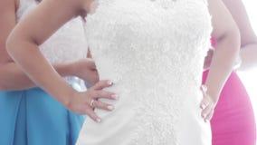 婚礼礼服的后方的特写镜头 换衣服的女傧相帮助 新娘为婚礼做准备 影视素材