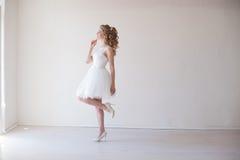 婚礼礼服的女孩在一个绝尘室婚礼站立 免版税库存图片