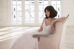 婚礼礼服的少妇在窗口前面的豪华内部开会 免版税库存图片