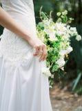 婚礼礼服的新娘与白色花束 免版税库存照片