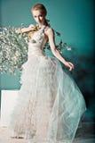 婚礼礼服的新娘在与花的灌木后 免版税库存图片