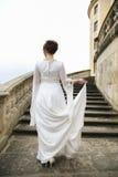 婚礼礼服的新娘在城堡台阶在多云天 库存照片