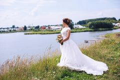 婚礼礼服的新娘在有花花束的河岸站立  免版税库存图片