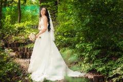 婚礼礼服的新娘在森林里 免版税库存图片