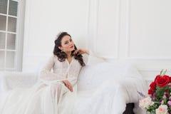 婚礼礼服的新娘坐长沙发 图库摄影