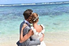 婚礼礼服的新鲜的新婚佳偶在加勒比岛上 免版税库存照片