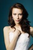 婚礼礼服的美丽的女孩在蓝色背景 免版税库存图片