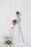 婚礼礼服的美丽的嫩典雅的女孩新娘与在头的冠在白色背景的演播室与花束在手上 免版税库存照片