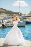 婚礼礼服的美丽的新娘与摆在白色的伞  免版税库存图片