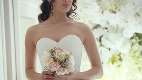 婚礼礼服的美丽的新娘与花在演播室 影视素材