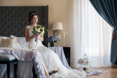 婚礼礼服的美丽的新娘与花花束  图库摄影