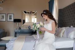 婚礼礼服的美丽的新娘与花花束  免版税库存照片