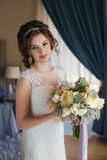 婚礼礼服的美丽的新娘与花花束  库存图片