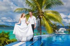 婚礼礼服的美丽的新娘与长的火车和新郎站立 免版税库存照片