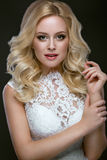 婚礼礼服的美丽的白肤金发的妇女与晚上构成、嫩嘴唇和卷毛 新娘图象 秀丽表面 免版税库存照片