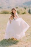 婚礼礼服的美丽的白肤金发的新娘横跨领域跑往山 免版税库存图片