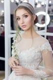 婚礼礼服的美丽的逗人喜爱的嫩女孩新娘在有晚上头发和柔和的轻的构成的镜子 免版税库存图片