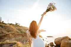 婚礼礼服的年轻美丽的妇女在海滩 免版税库存照片