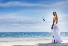 婚礼礼服的年轻美丽的妇女在热带海滩 免版税库存图片