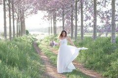 婚礼礼服跳舞的美丽的时髦的新娘在春天森林里 免版税库存图片