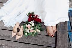 婚礼细节:新娘脚、花束和鞋子 免版税库存照片