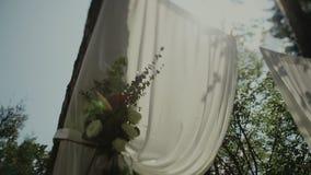 婚礼花曲拱装饰 用花装饰的婚礼曲拱在公园 太阳断裂通过树 股票录像