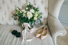 婚礼花束、桃红色新娘鞋子和黑匣子有圆环的在豪华沙发 户内 附庸风雅 免版税库存照片