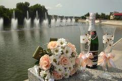 婚礼花束、酒杯和香槟在喷泉Roshen的背景 免版税库存照片