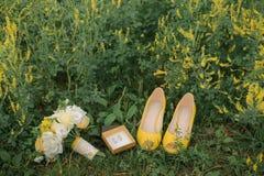婚礼花束、鞋子和圆环在草 库存照片