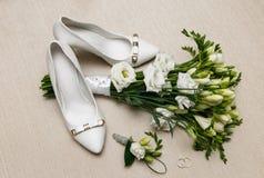 婚礼花束和女傧相鞋子、钮扣眼上插的花和圆环 图库摄影