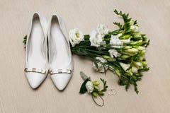 婚礼花束和女傧相鞋子、钮扣眼上插的花和圆环 免版税库存照片