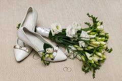 婚礼花束和女傧相鞋子、钮扣眼上插的花和圆环 免版税库存图片