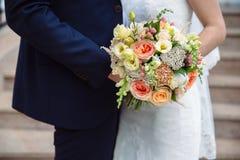 婚礼花束在婚姻夫妇手上 免版税库存照片