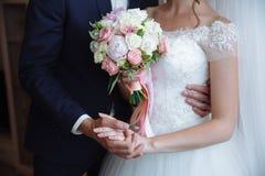 婚礼花束在婚姻夫妇手上 库存图片