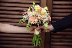婚礼花束在婚姻夫妇手上 免版税库存图片