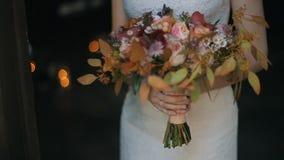 婚礼花束在户内新娘手上 在背景的灼烧的蜡烛 新娘拿着美丽的婚礼花束  股票录像