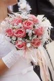 婚礼花束在新娘的手上一件白色礼服的 库存照片