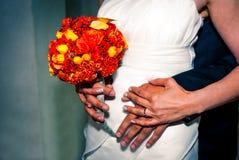 婚礼花束在新娘的手上,用在她附近的新郎的手 库存图片