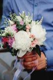 婚礼花束在新郎手上 免版税库存照片