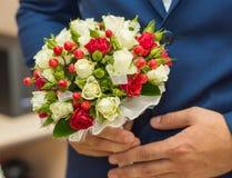 婚礼花束在新郎的手上 免版税库存图片