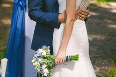婚礼花束在美丽的新娘的手上白色婚礼礼服的 免版税库存图片
