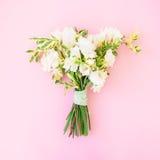 婚礼花束由白花制成在桃红色背景 平的位置,顶视图 背景看板卡问候页模板通用万维网婚礼 免版税库存图片