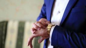 婚礼衣服的时髦的加工好的新郎嘲笑手手表 关闭上色百合软的查阅水 股票视频