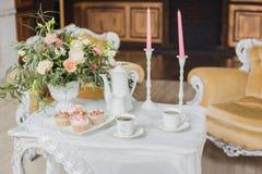 婚礼装饰区域-与花束和杯形蛋糕的白色桌 免版税库存图片